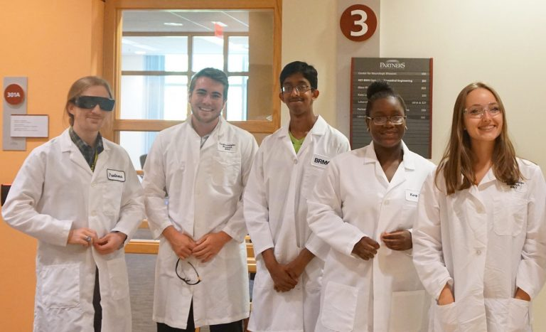 Students wearing lab coats prepare for a medical experiment at Boston Leadership Institute