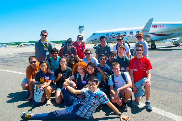 Students pose in front of airplane in the Applied Physics and Engineering three-week summer program