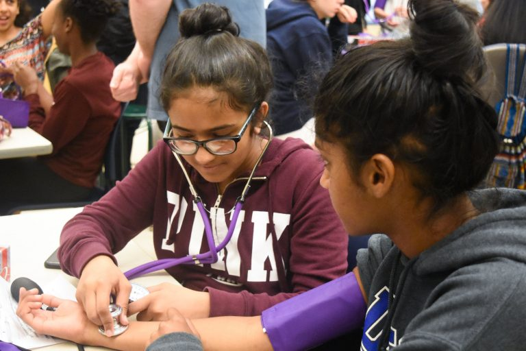 Students do tests using a stethoscope in the Pediatrics one-week summer medical program