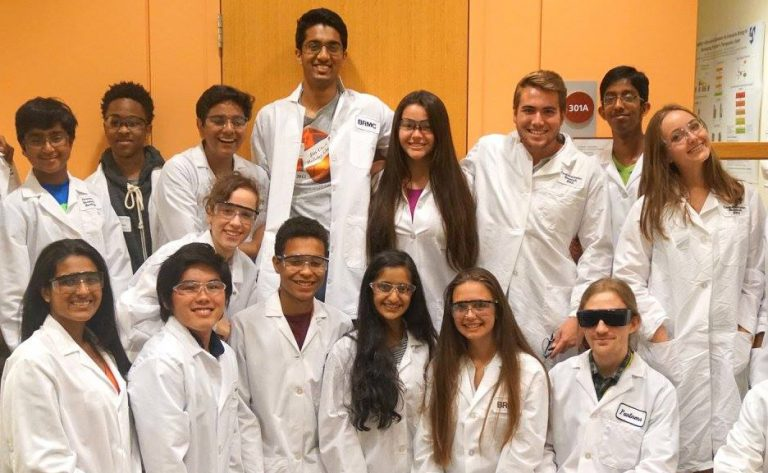 Students pose while wearing lab coats in the Biomedical and Surgical Research three-week summer program