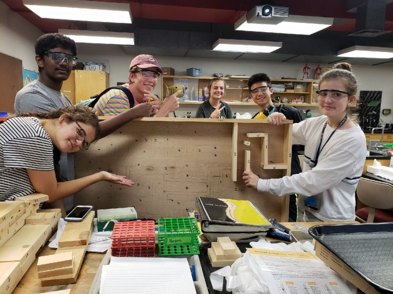 Students show off part of the experiment they built in the BioTech and Pharma Research three-week summer science program