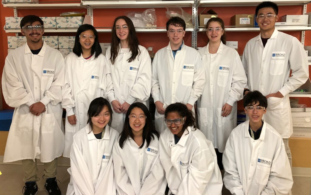 Students pose while wearing lab coats in the Emergency Medicine three-week summer medical program