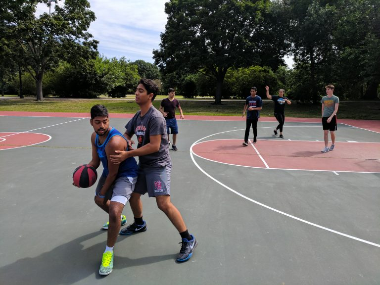 Students play basketball at the Fens in Boston