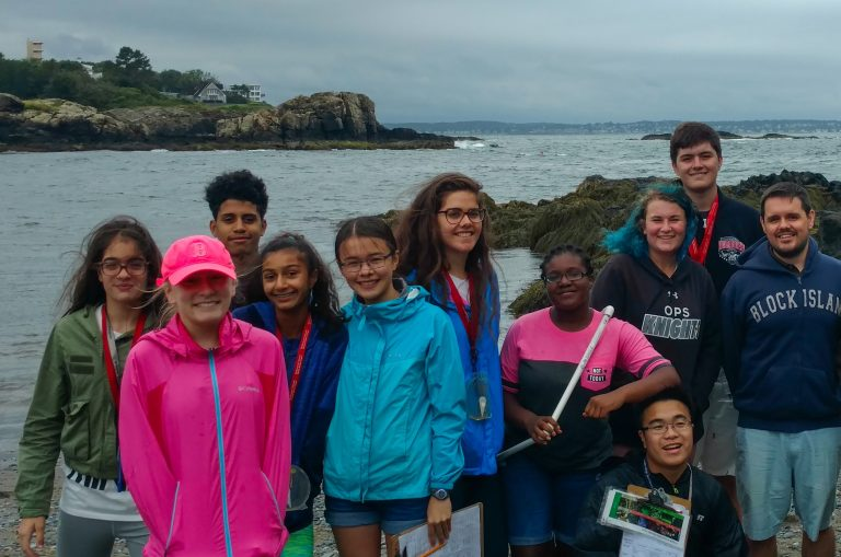 Teacher Steve Smith poses with students off the coast of Boston in the Marine Biology three-week summer science program