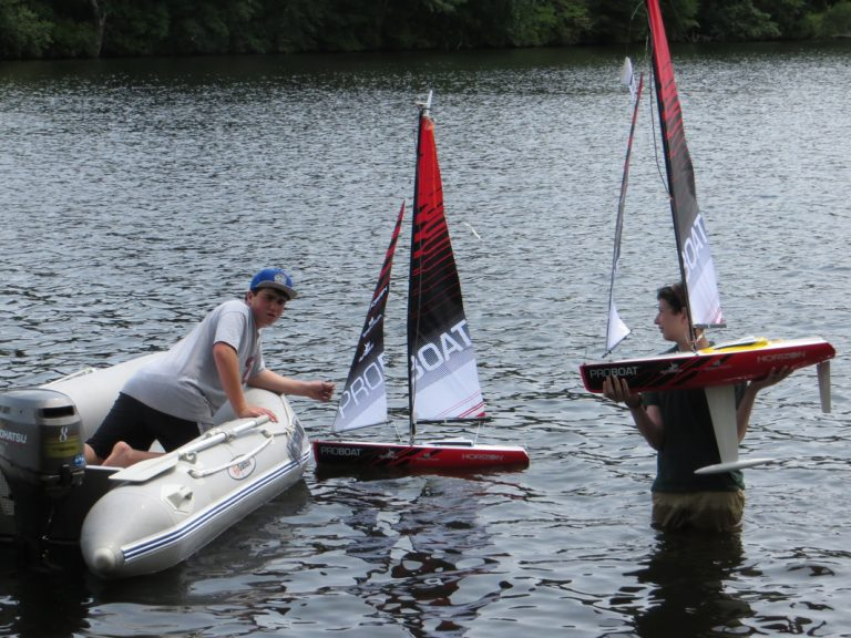 Students set up their remote-controlled boats in the water in the Engineering Research three-week summer engineering program