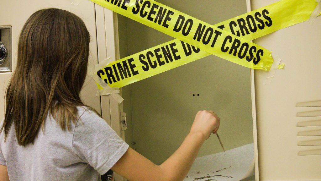 Student sets up a mock crime scene in the Forensics one-week summer science program