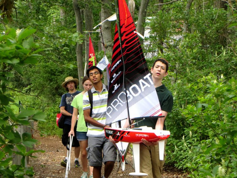 Students bring their remote-controlled sailboats to the water in the Engineering Research three-week summer engineering program