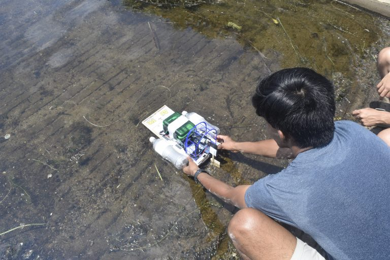 Students pilot their remote-controlled boats in the Engineering Research three-week summer engineering program