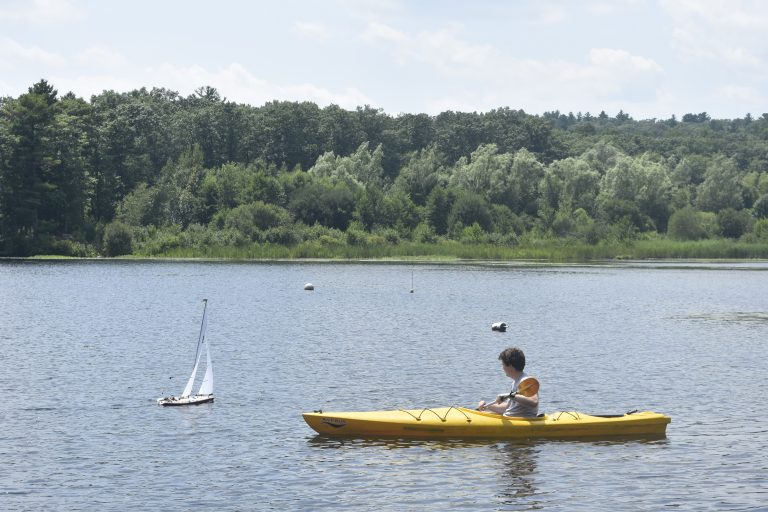 Student follows remote-controlled boat in a kayak in the Engineering Research three-week summer science program