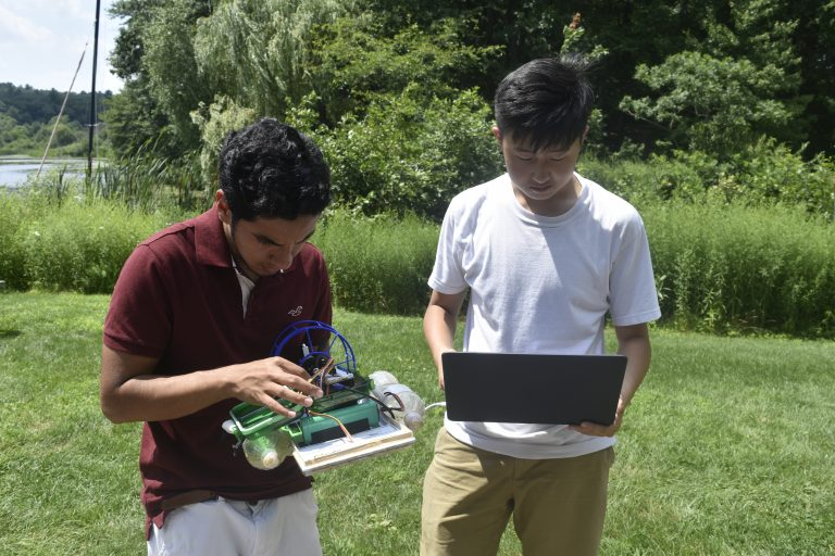 Students do work on their remote-controlled boat in the Engineering Research three-week summer engineering program