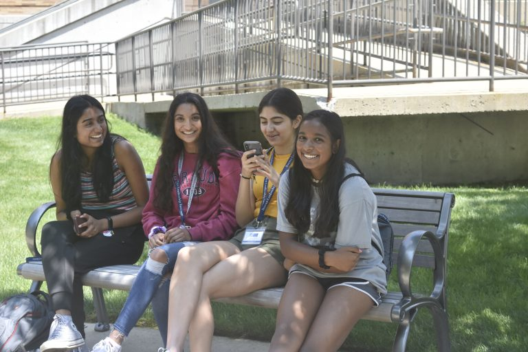 Students relax on a bench after lunch in the Longwood campus